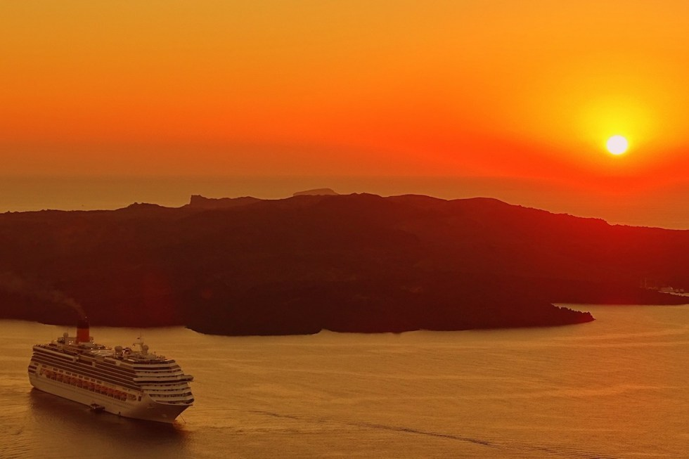A ferry boat on a cruise near Santorini, Greece during sunset.