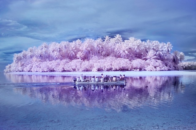 A boat full of people riding back from one of the uninhabited islands around Pingelap, photographed with infrared filters by Sanne De Wilde.