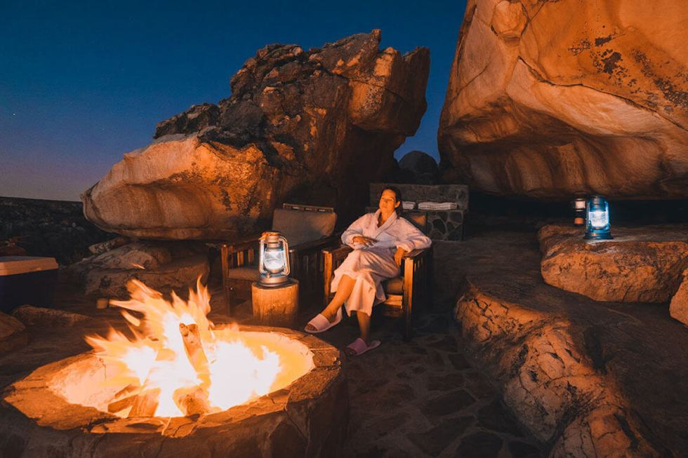 Woman relaxing near the fire pit at the Kagga Kamma Star Suite in South Africa.