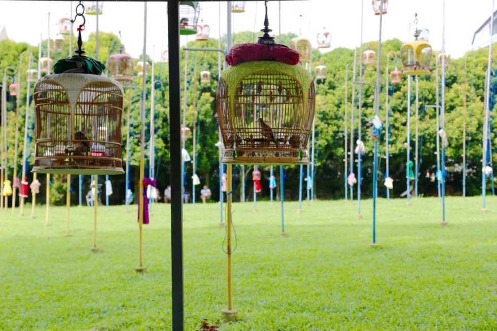 Ornate cages dangling from tall poles at the Kebun Baru Bird Singing Club in Singapore.