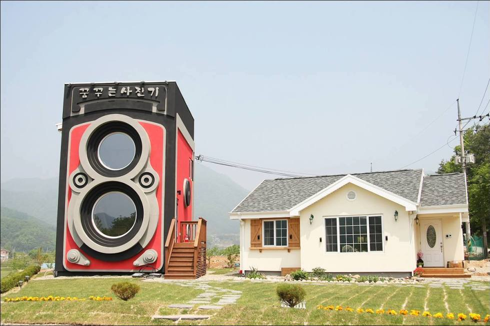 The Dreamy Camera Cafe (constructed in the shape of a Rolleiflex Twin Lens Camera) next to a cute little residence in Yangpyeong county, South Korea.