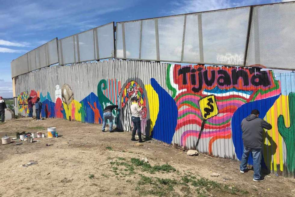 "Volunteers painting a small segment of Enrique Chiu's project, ""Mural of Brotherhood,"" on the US-Mexico border wall."