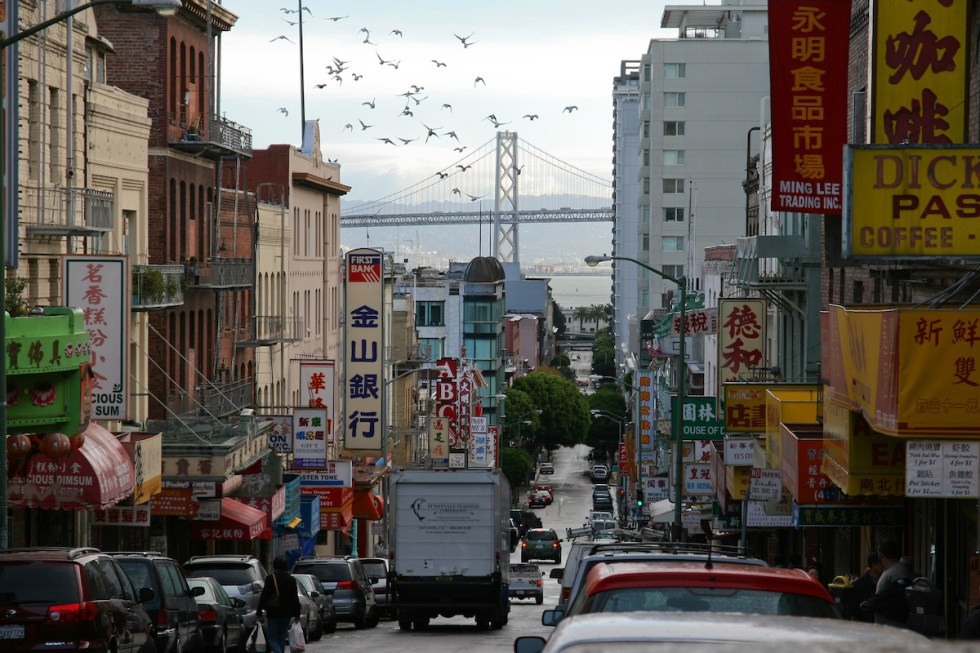 Chinatown businesses in San Francisco with the Bay Bridge in the background