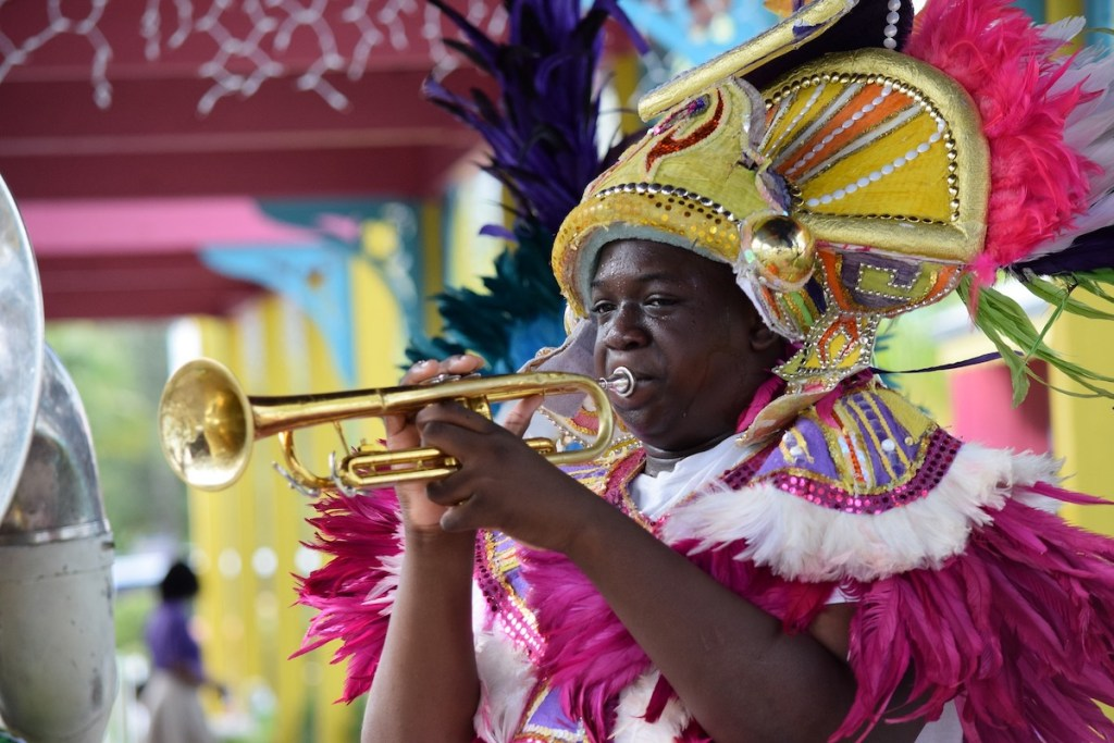 Man dressed in a colorful costume and playing a brass horn during Junkanoo celebrations in the Bahamas.