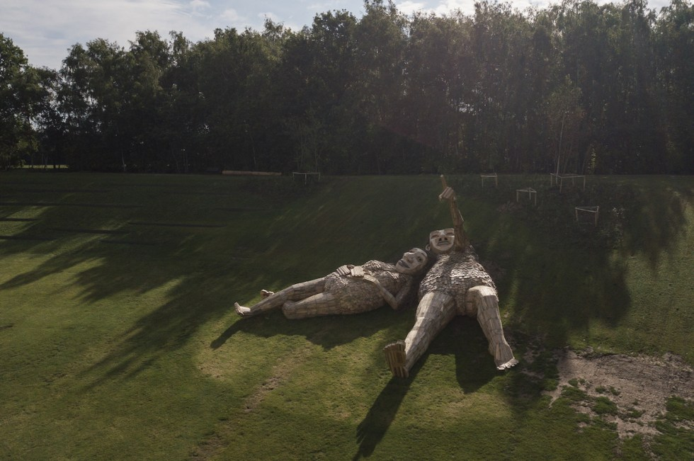 Two giant trolls laying in the grass