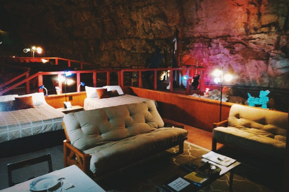 Double beds, couches, coffee table and dining table inside the Grand Canyon Caverns Underground Suite in Arizona