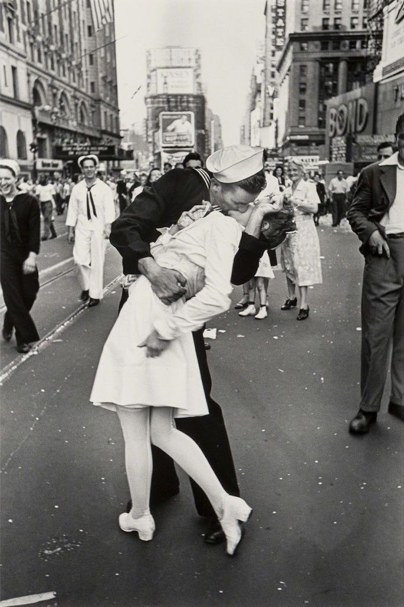 """""""V-J Day in Times Square,"""" a photograph by Alfred Eisenstaedt. It was published in Life Magazine in 1945 with the caption, """"In New York's Times Square a white-clad girl clutches her purse and skirt as an uninhibited sailor plants his lips squarely on hers."""""""