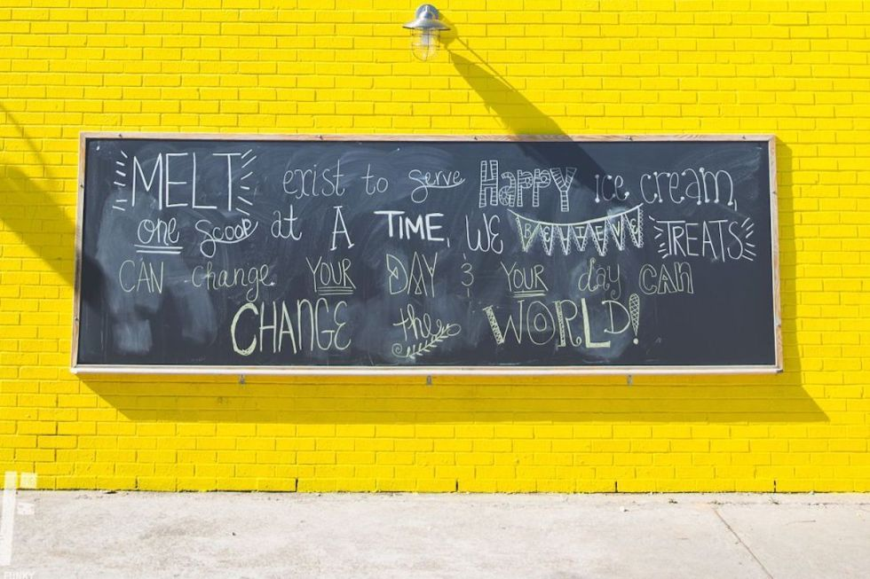 Blackboard on a yellow brick wall outside Melt Ice Cream