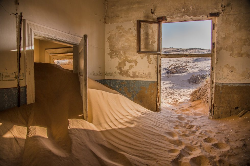 abandoned home at Kolmanskop ghost town flooded with windswept sand dunes