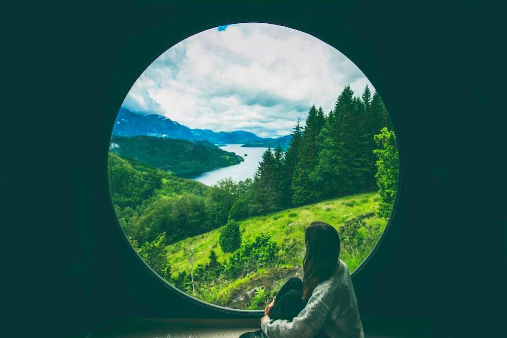 woman gazing over Norway's wild fjords and lush valleys from a Livit birdbox