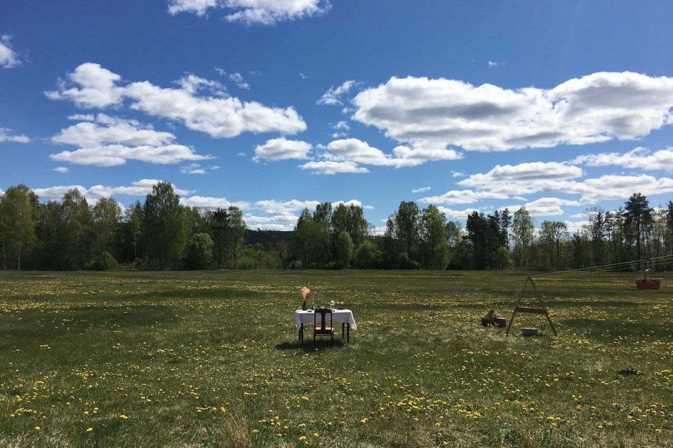 one table, one chair, and a picnic basket in the middle of a lush meadow in Värmland, Sweden