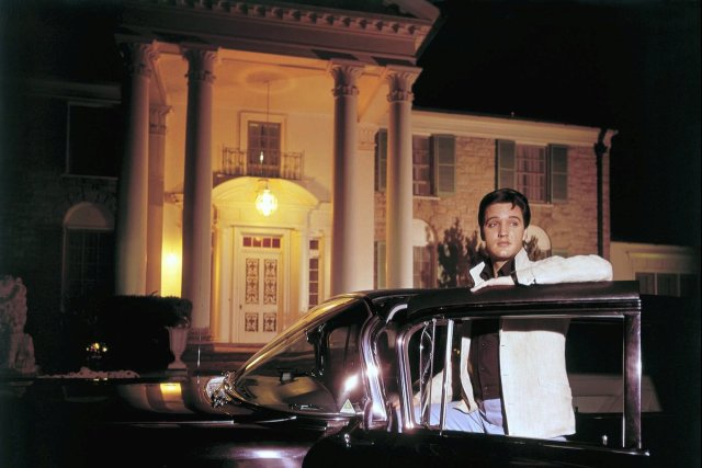 Elvis posing with one of his cars outside Graceland