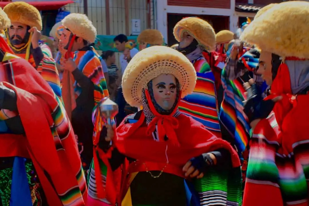 A parachico, a masked man dressed in colorful garb, dancing in the streets at the Fiesta Grande de Chiapa. A must see if visiting in January.