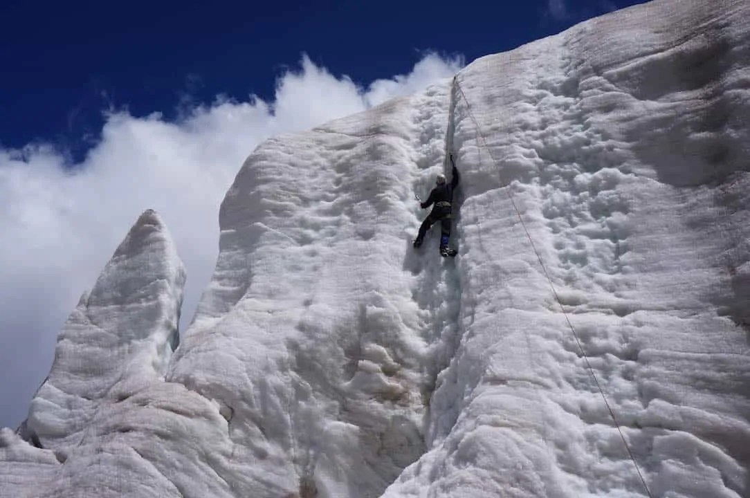 Scaling a sheer cliff of ice with ice axes and crampons