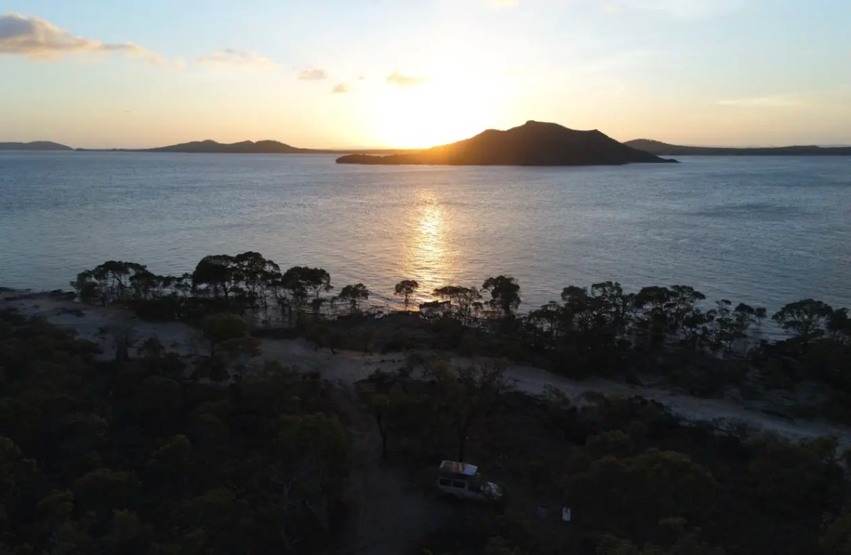 The sunsetting over an island with a car on the mainland at one of the best free camping Queensland has to offer in Cape York.