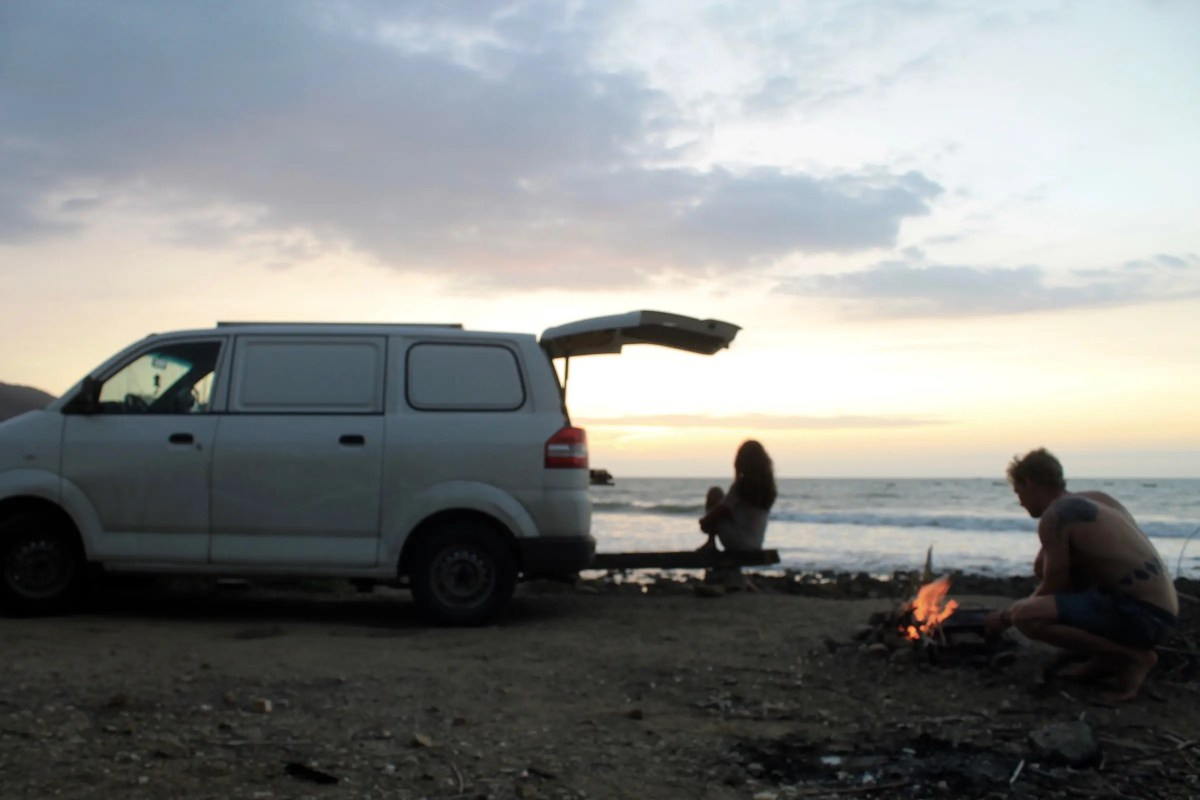 A girl looking out to sea while a boy preps a fire in the shadows of a van at Pueblo Nuevo, one of the best beaches in Ecuador.