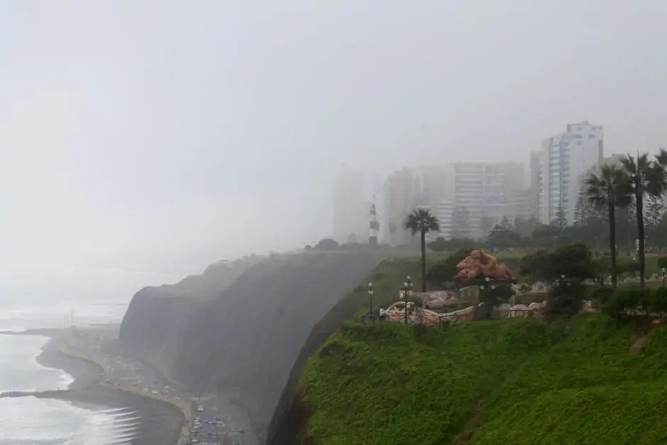 "A gloomy view along the Miraflores promenade, one of the best things to do in Lima on a one day trip in Lima, overlooking the Miraflores cliffs and the ""el Beso"" statue"