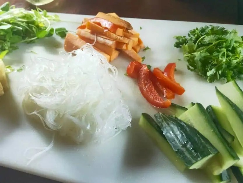 Some fresh ingredients for rice paper rolls including carrot, cucumber, vermicelli noodles, coriander, and bell pepper. An easy van life meal on the road.