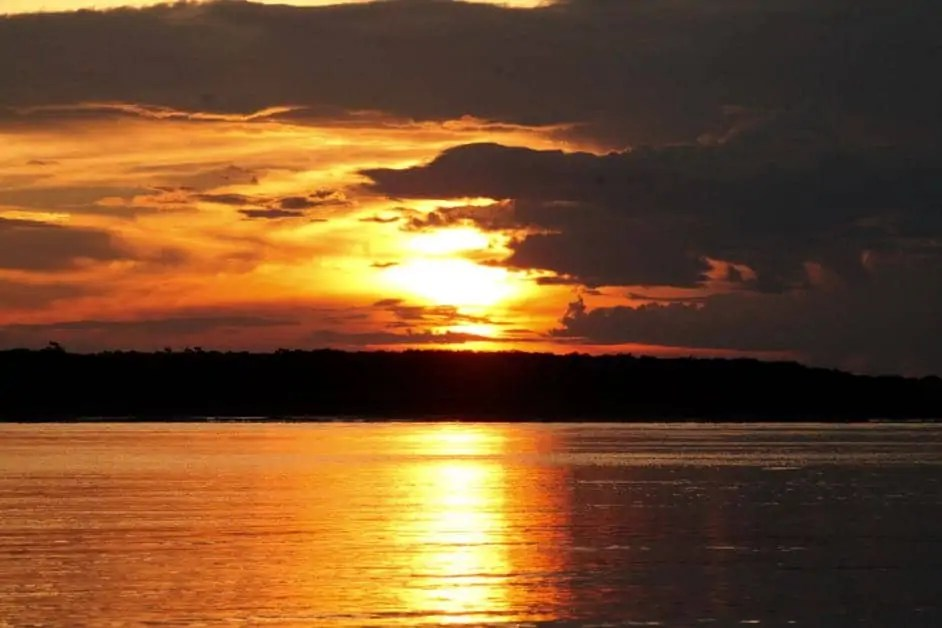 The yellow and orange sunset over the Yarapa River on an excursion with The Treehouse Lodge Peru in the Amazon jungle.