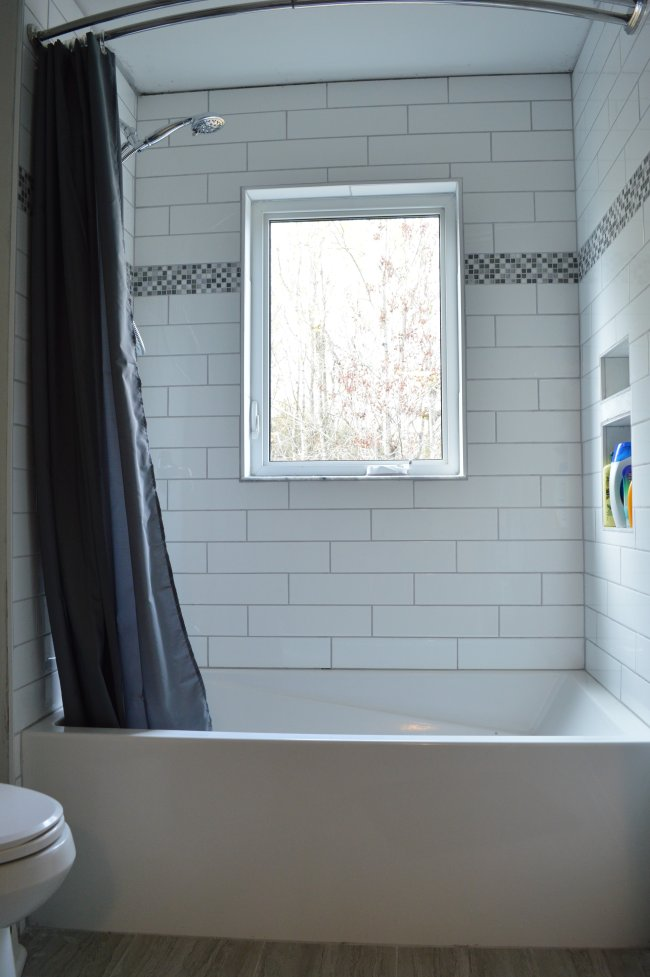 Subway tile shower with mosaic tile accent