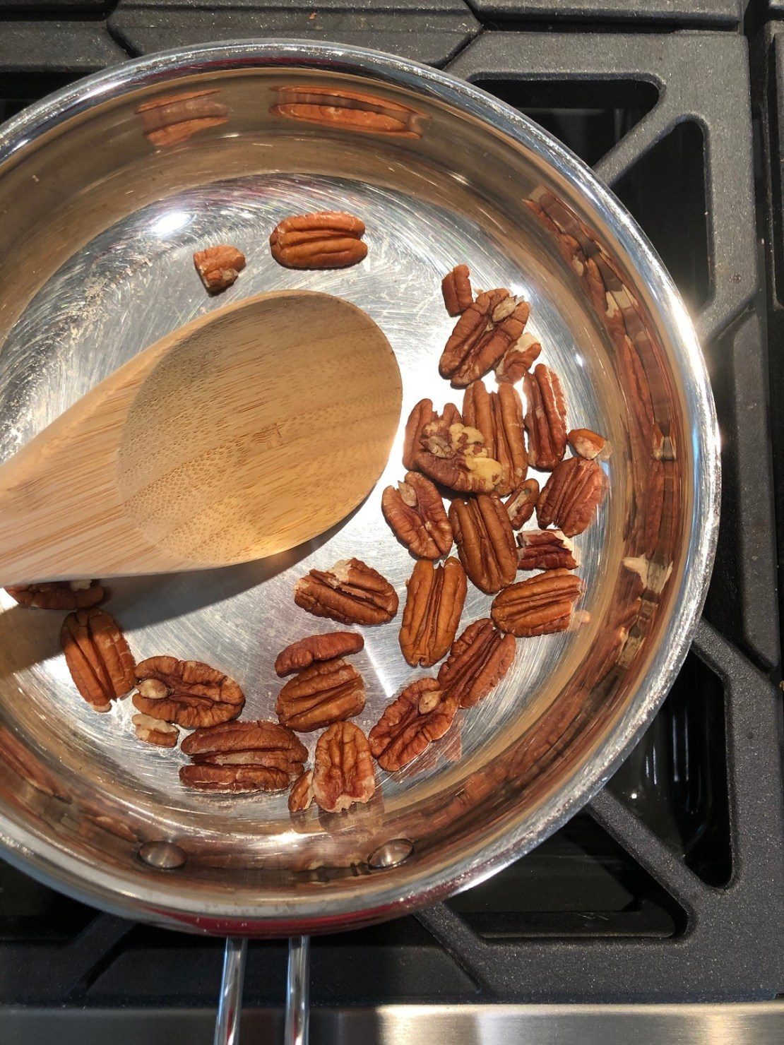 roasted pecans in stainless steel pan on stove with wooden spoon