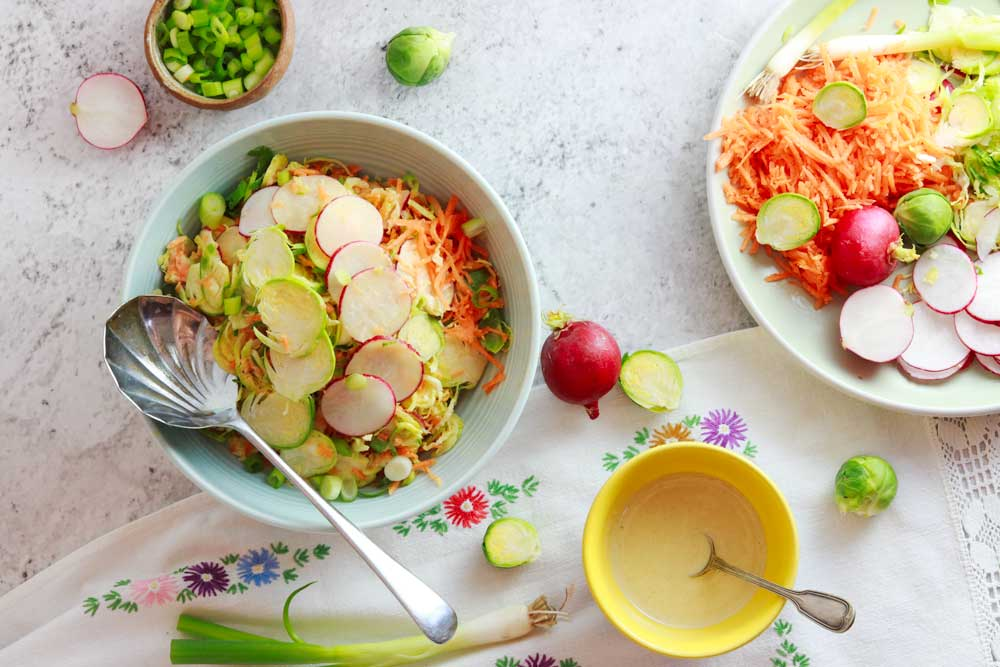 Winter Disco Slaw with Brussel Sprouts on a table with more dressing