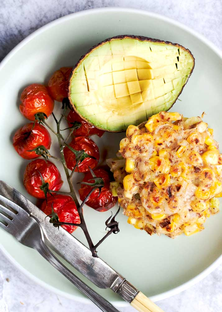 Close up of corn cake on a plate with avocado and roasted tomatoes