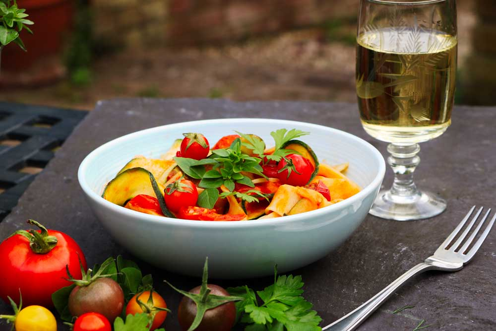 Zucchini and tomato pasta with herbs on top