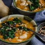 Butternut Squash and White bean soup in a bowl with a spoon.