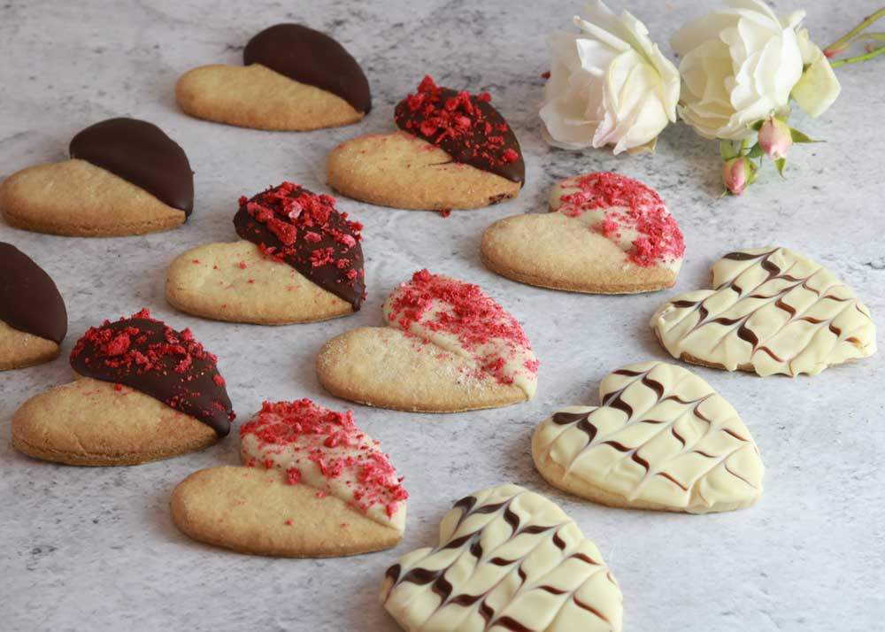 Rows of heart shaped Valentines biscuits with a rose in the background