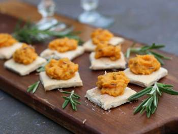 Vegan Carrot and Carroway dip on Rosemary Sea Salt Crackers on a board with drinks in the background