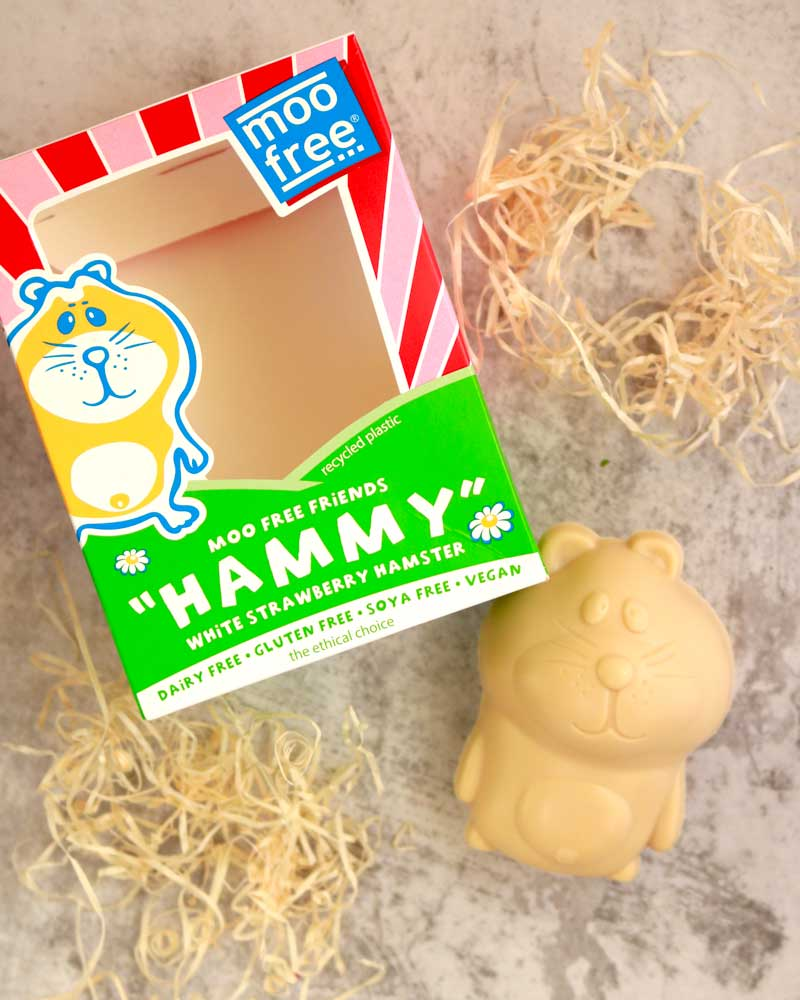 vegan white chocolate shaped like a hamster, next to it's packaging box and with straw