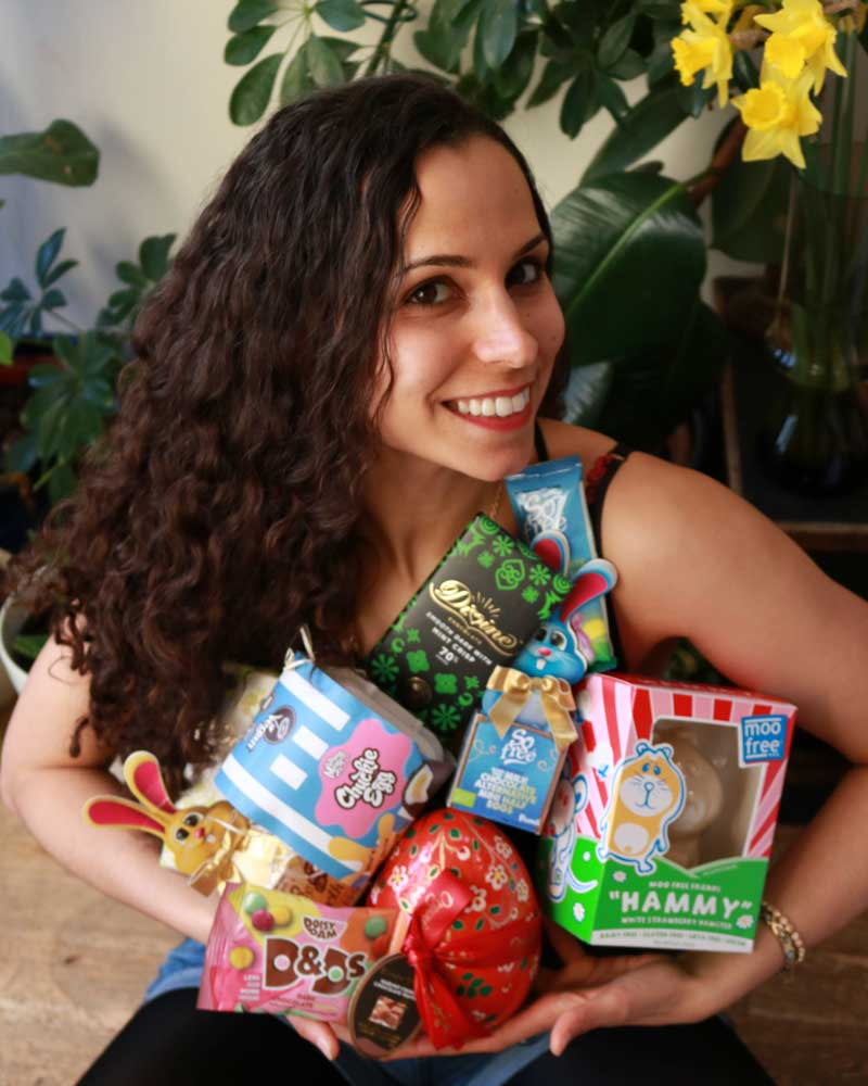 Vanessa from the vegan larder holding all the vegan easter chocolate products