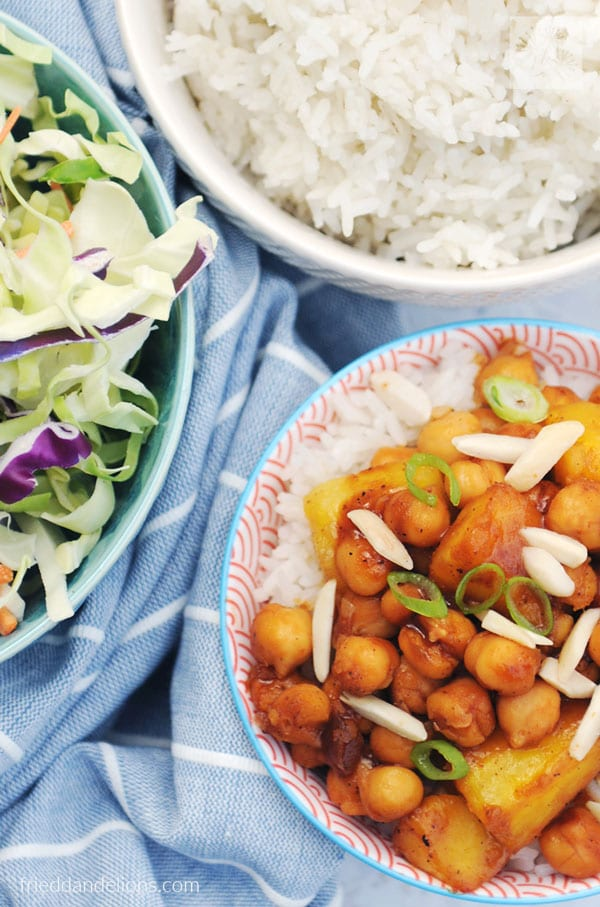 Chickpea pineapple stir fry in a bowl with rice and salad