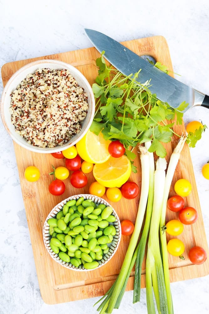 Ingredients for quinoa tabboleh salad on a board