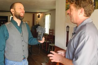 Two men talk in an old kitchen