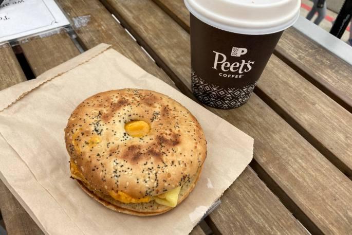 Peet's vegan breakfast sandwich on a wood table with a small oatmilk vanilla latte.