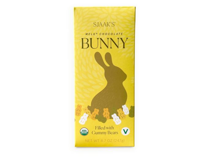 Sjaak's brand yellow packaging for vegan milk chocolate easter bunny with gummy bears inside.