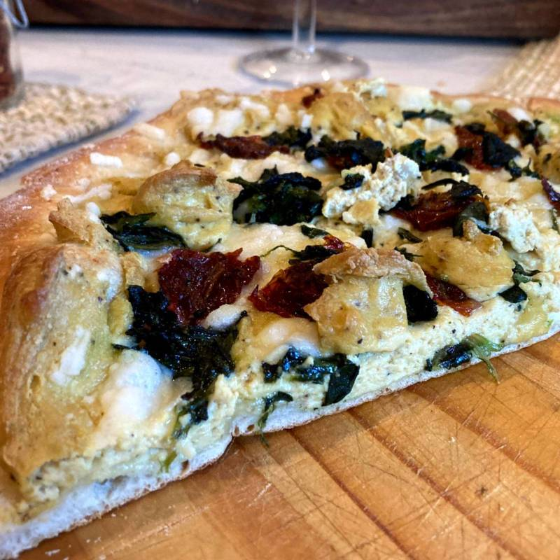 Vegan white pizza with tofu ricotta, spinach and sun-dried tomato on a cutting board.