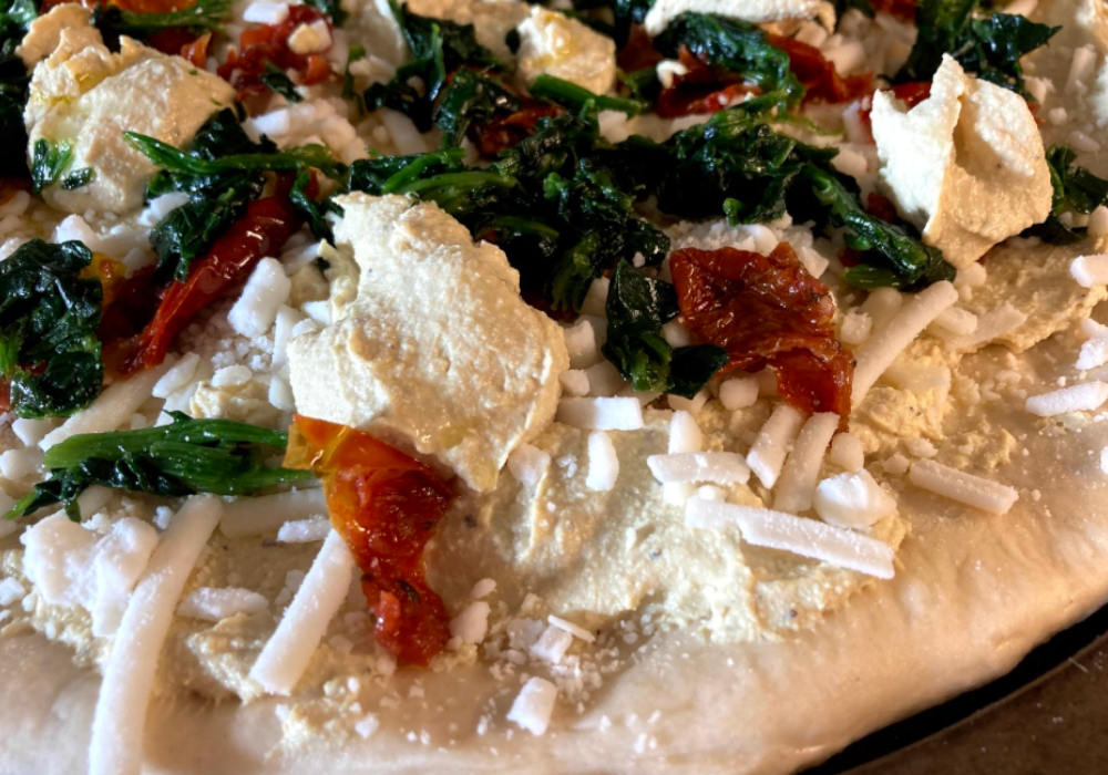 Vegan white pizza with spinach, sun-dried tomatoes and vegan ricotta pre-bake.