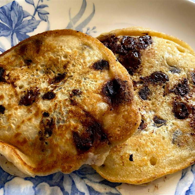 Blue and white floral plate with 2 vegan chocolate chip pancakes on it.