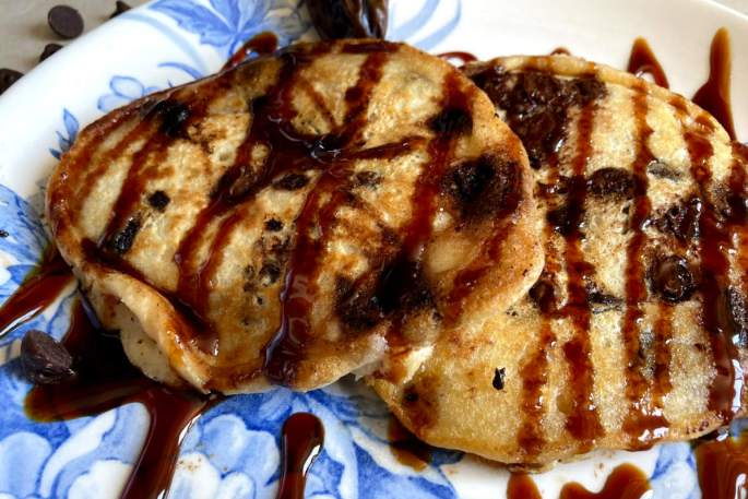 Vegan chocolate chip pancakes on a blue and white floral plate drizzled with date syrup.