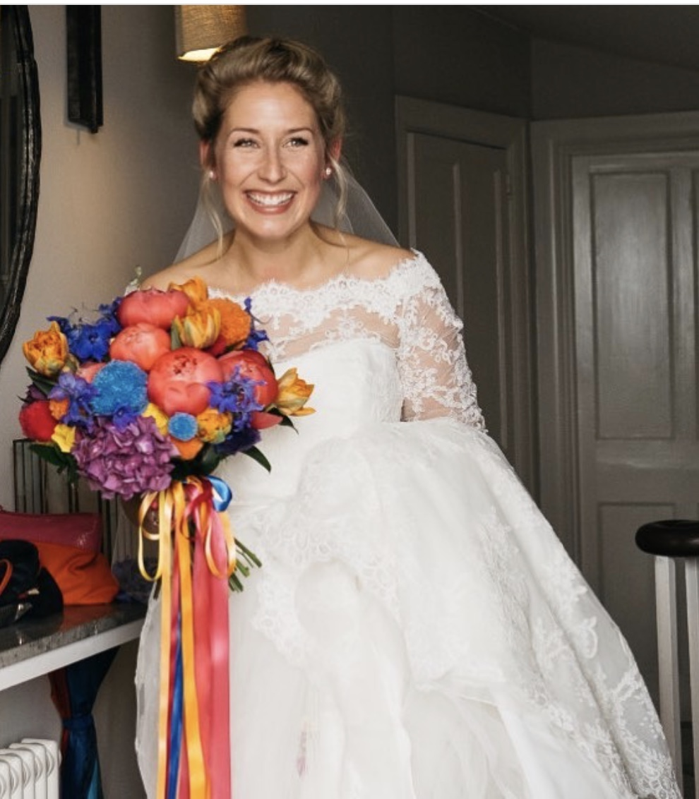 Happy bride holding bespoke colourful flowers
