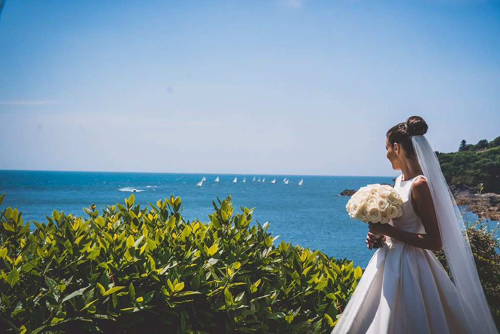 A bride looking towards the blue sea on a sunny day holding her bouquet of cream roses