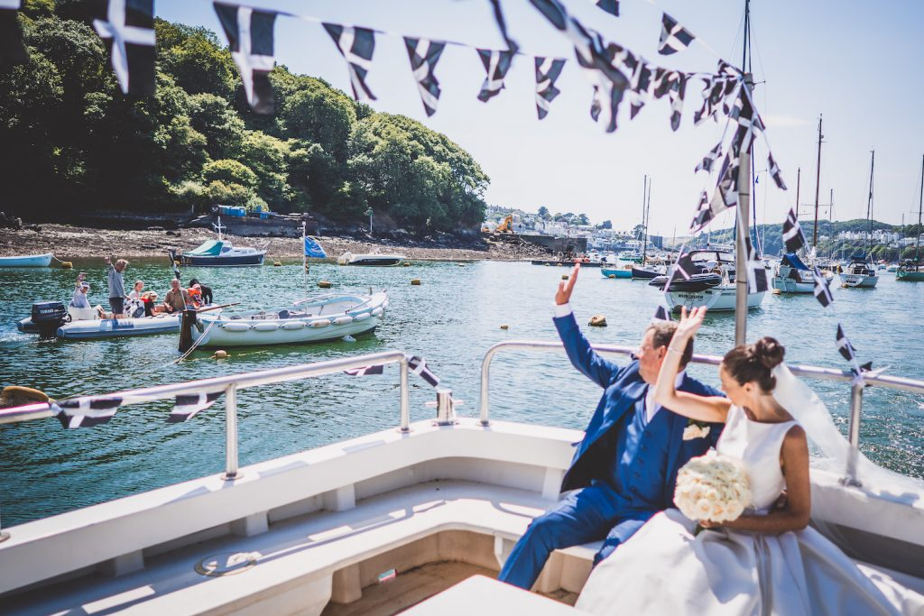 Wedding couple in a boat on the sea waving to other sailors. A real summer seaside wedding in Cornwall