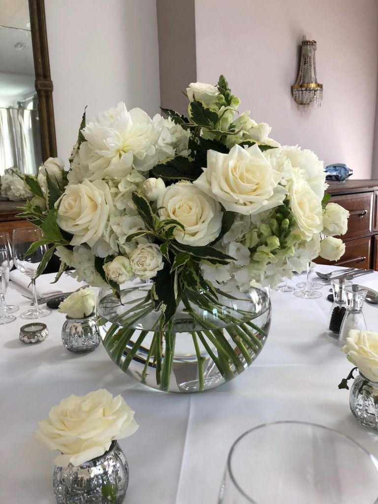 A guest table arrangement with roses, hydrangea and stocks in a large clear glass fishbowl with small tealights holding a single bite rose.