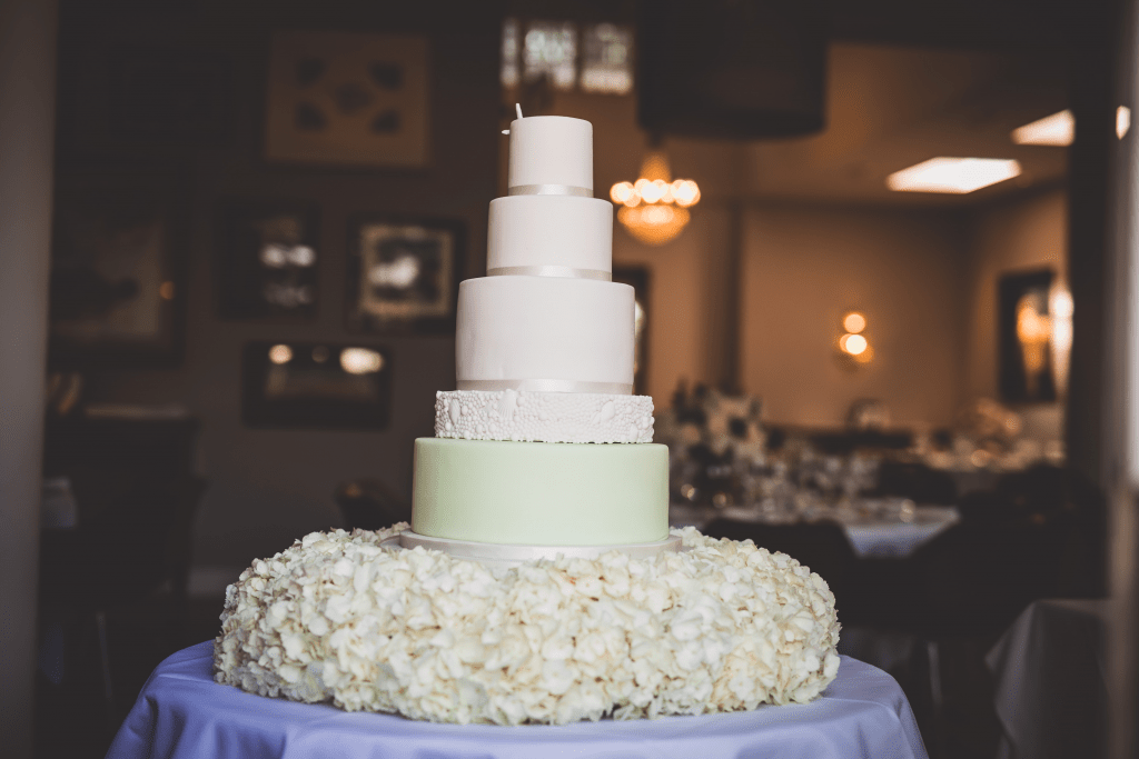 Tall, pale green and white wedding cake with a collar around the based made of cream hydrangeas