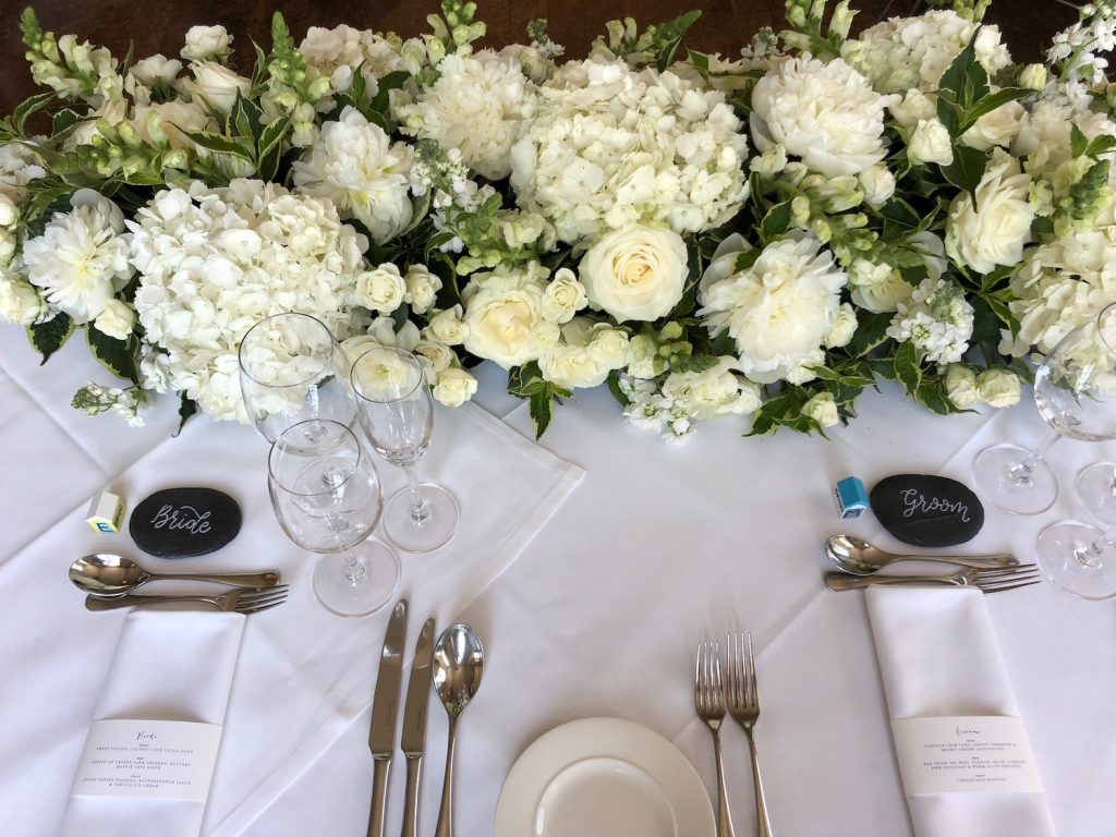 A green and white hydrangea with white roses on top table arrangement at a classic wedding. A real summer seaside wedding in Cornwall
