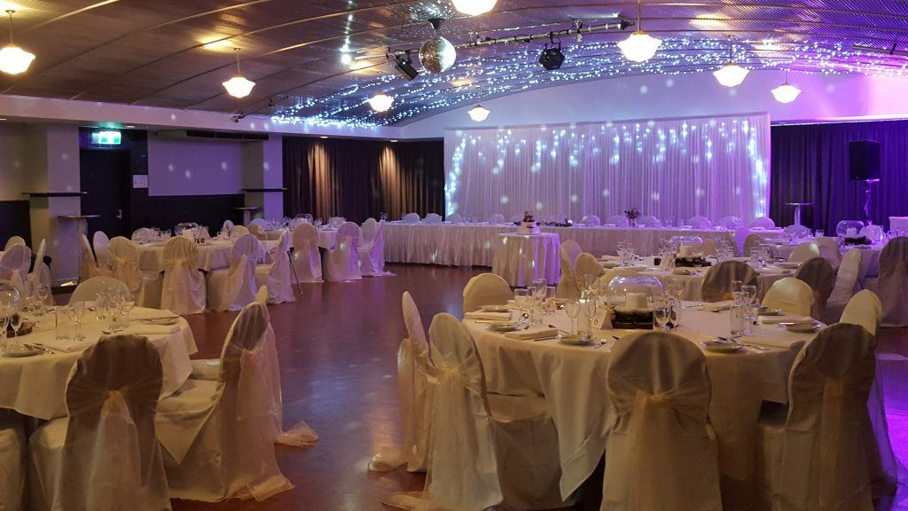champagne wedding; fishbowl centrepieces; purple lights; fairy lights; big bridal table; round tables; fannie bay