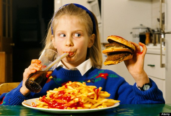 Young schoolgirl eating a huge hamburger and chips drinking coke at home in after school London HOMER SYKES